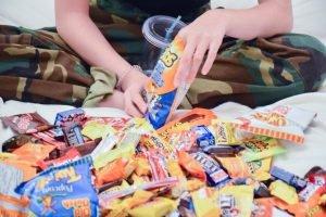 Tânără înconjurată de dulciuri și snacksuri