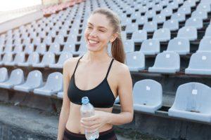 Tânără se hidratează după o sesiune de alergare