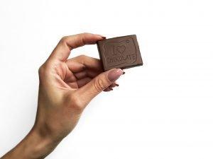 Tânără ține în mână un pătrățel de ciocolată