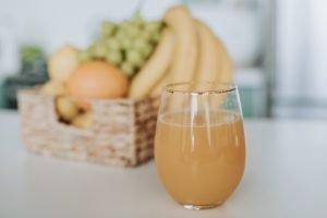 Suc natural de portocale și un coș cu fructe