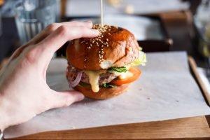 Tânăr măsoară cu degetele dimensiunile unui burger