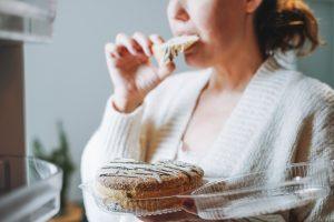 Tânără în halat în casă mănâncă seara o prăjitură din frigider
