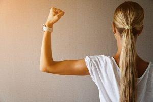 Tânără își încordează mușchii brațului