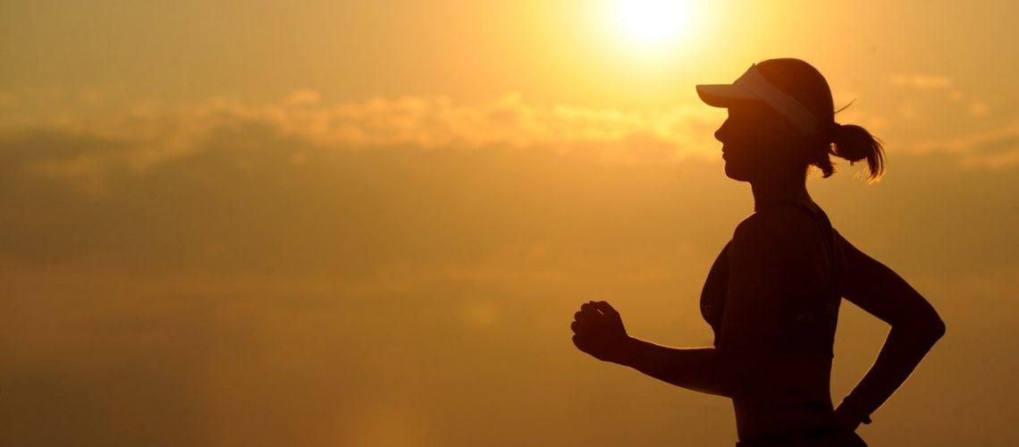 Femeie care face jogging la apus.